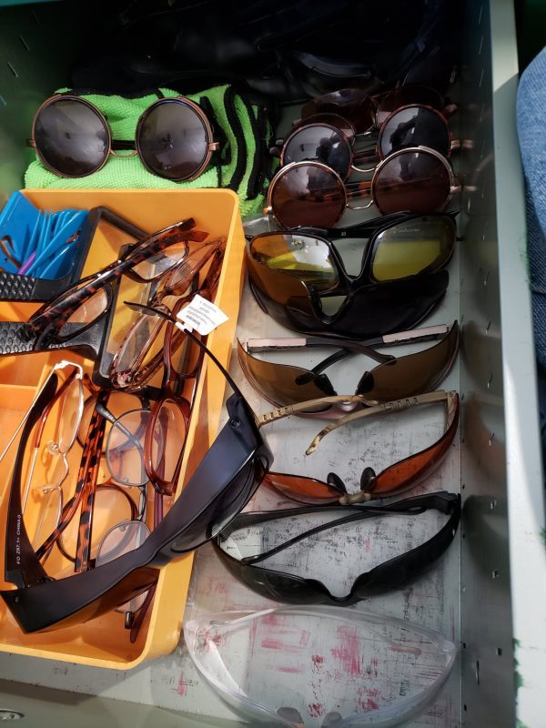 desk drawer full of sunglasses